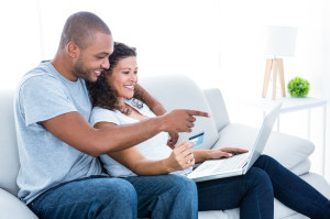 45312173 - couple enjoying online shopping sitting on sofa at home
